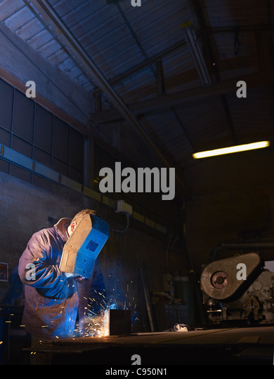 Manual worker in steel factory using welding mask, tools and machinery on metal. Vertical shape, side view, waist - Stock Image