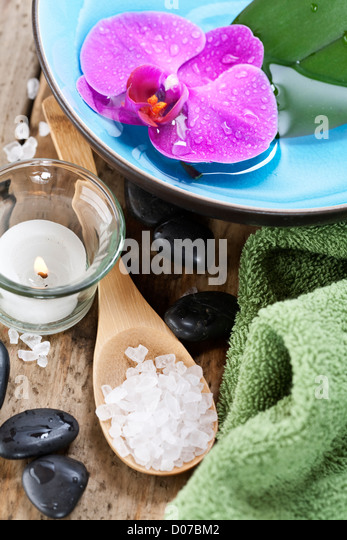 Spa Settings (zen stones, candle, towel, sea salt and orchid) - Stock Image