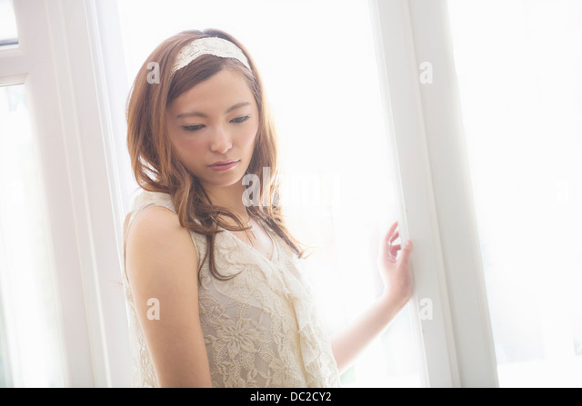 Woman with sad face looking down - Stock Image