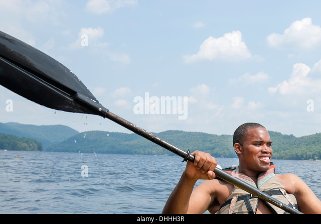 Young man wearing life vest holding oar - Stock Image