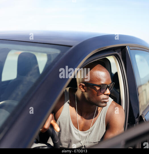 Afro american guy sitting in his car looking away. Muscular young man at the wheel of his car. - Stock Image