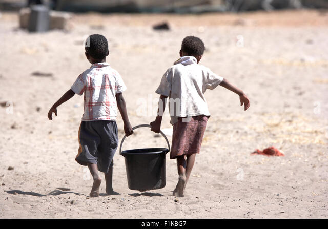 Two bushman children carrying a bucket of water, Xai Xai, Botswana - Stock Image