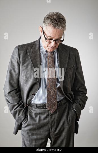 Senior man with hands in pockets, looking down - Stock-Bilder