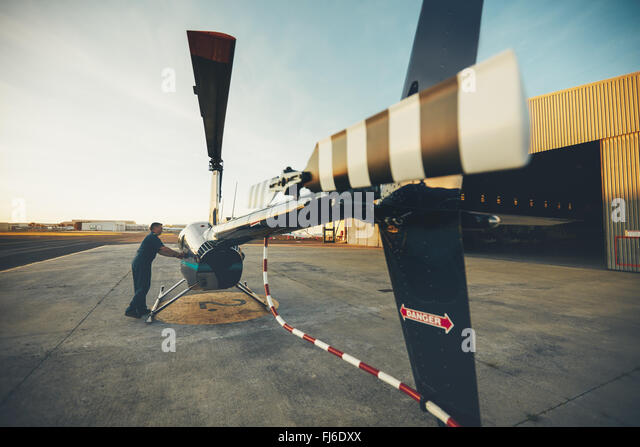 Male pilot inspecting helicopter before take off. Pilot preparing his helicopter for flight - Stock Image