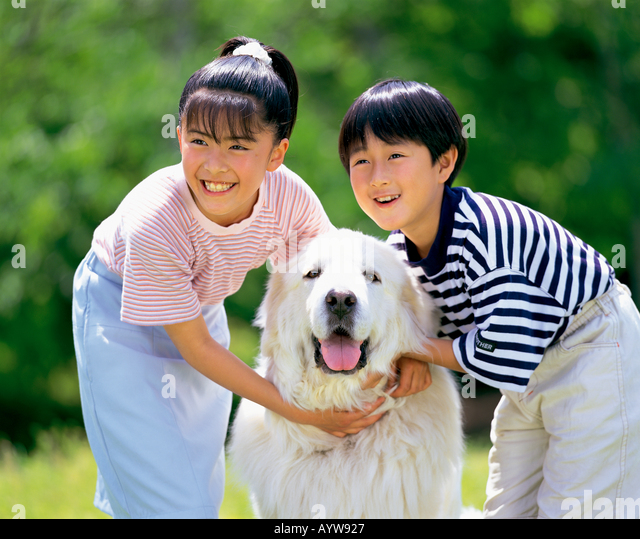 Boy and girl with big white dog - Stock-Bilder