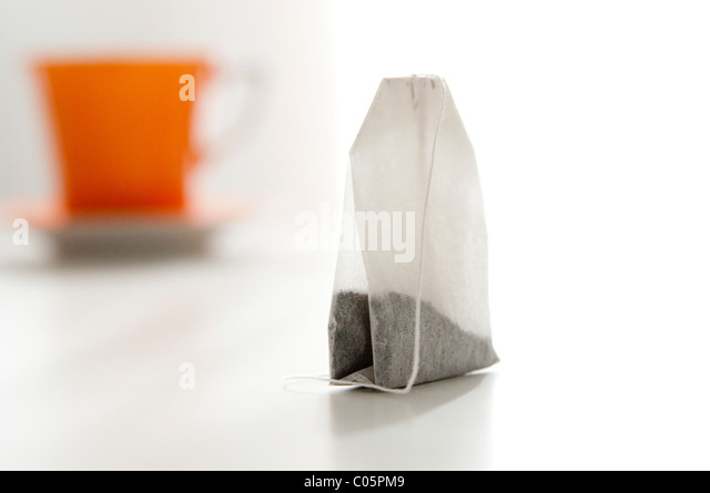 close up of tea bag with out of focus orange tea cup in background - Stock-Bilder