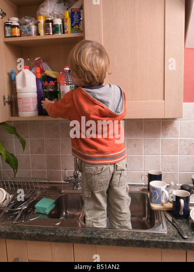 toddler boy child reaching dangerous kitchen cupboards by standing in sink - Stock Image