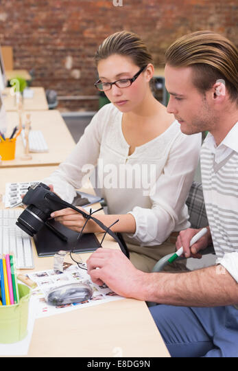 Concentrated photo editors looking at camera in office - Stock Image