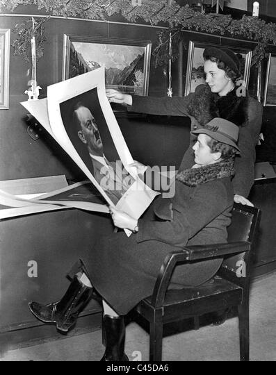 Two women looking at illustrations, including a portrait of Hitler, 1937 - Stock-Bilder