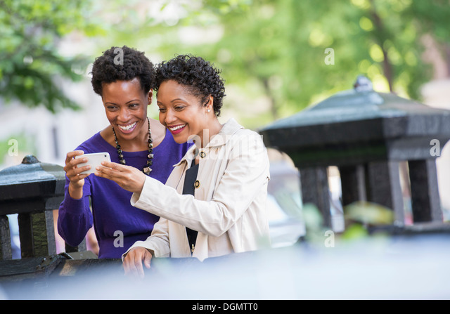 City life. Two women sitting on a park bench, looking at a smart phone. - Stock Image