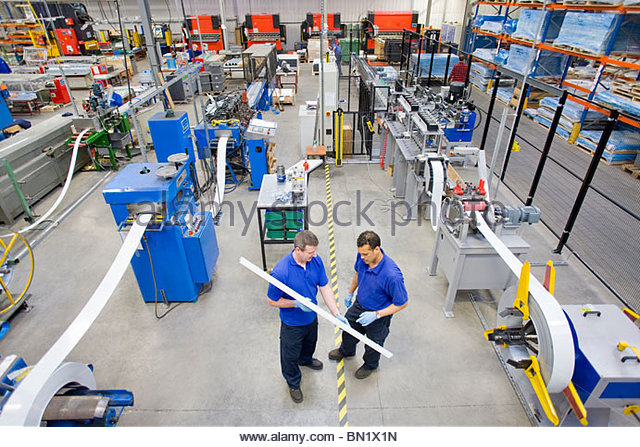 Workers inspecting aluminium light fitting in factory - Stock-Bilder
