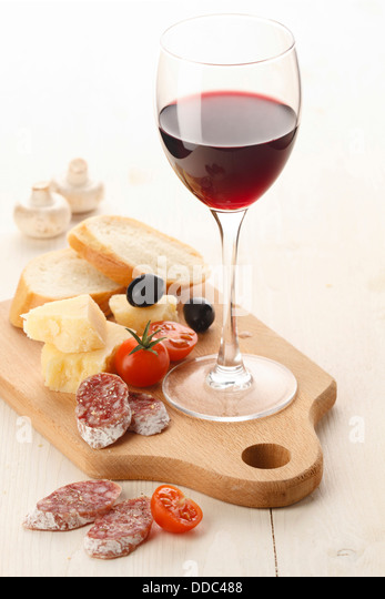 Wineglass with red wine and assortment of cheese and fruits on white background - Stock-Bilder