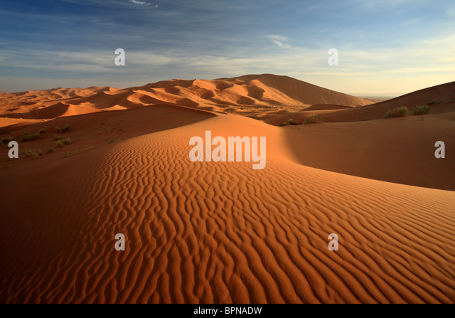 Light and shadow play at sunrise across the dunes of Erg Chebbi near Merzouga in Morocco - Stock Image