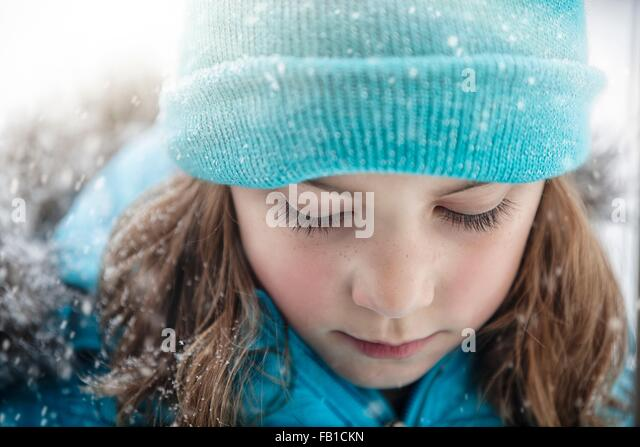 Close up portrait of girl wearing knit hat looking down, snowing - Stock Image