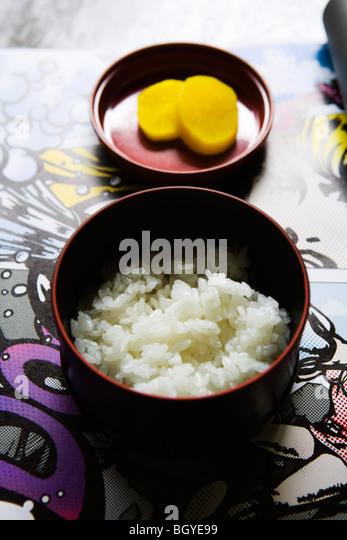 Bowl of white rice, pickled radish side dish - Stock Image