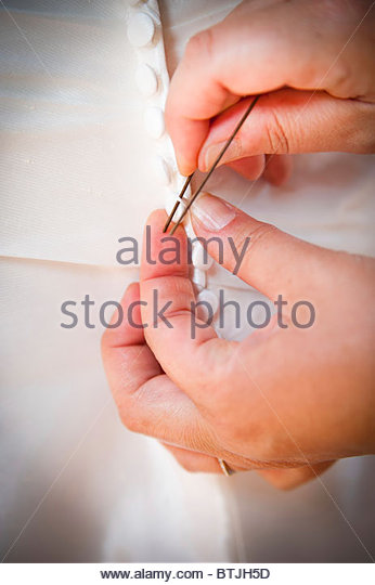 Hands buttoning up the bride's wedding dress - Stock Image