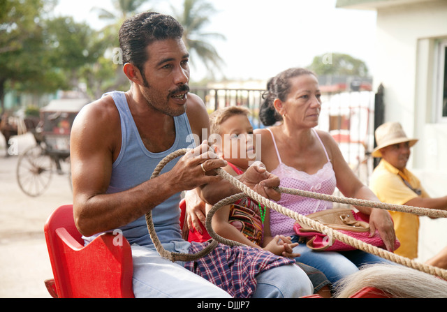 A cuban family comprising mother, father and son, in a horse and carriage, Havana, Cuba, Caribbean - Stock Image