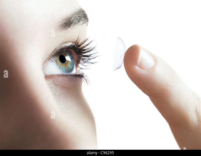 Contact lens use. Woman putting in a contact lens. - Stock Image
