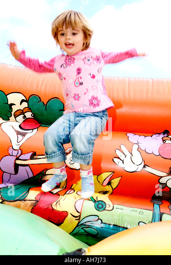 happy child playing on a bouncy castle play fun enjoy enjoyment fun bounce jump spring energy hyperactive smile - Stock Image