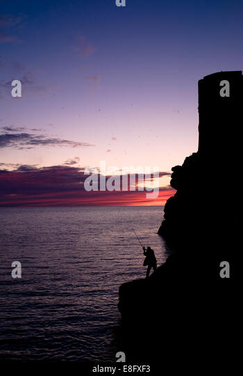 Croatia, Dubrovnik-Neretva, Dubrovnik, Silhouette of man fishing from rock formation - Stock Image