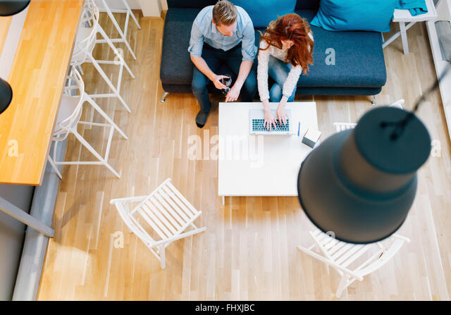 Couple browsing web together in living room viewed from above - Stock Image