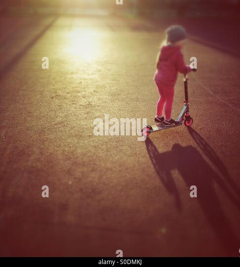 Child riding scooter - Stock-Bilder