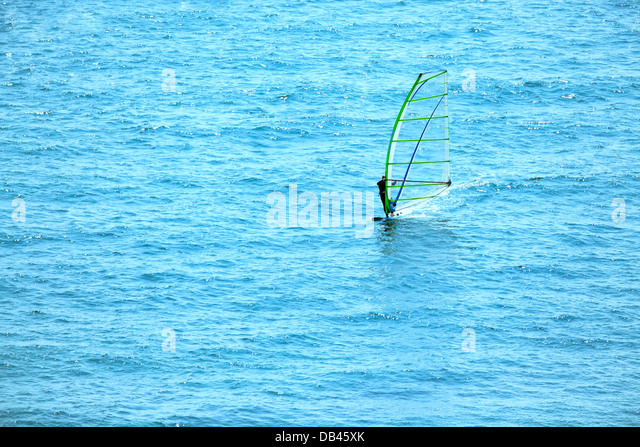 Wind Surfing Surfer On The Ocean. Surfer from Right To Left With Copy Space On The Left. Beautiful Blue Aqua Colored - Stock Image