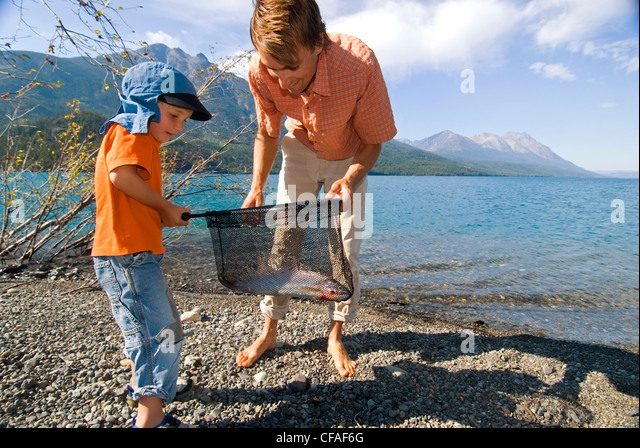Father and son catching trout in a net on a fishing trip, Tatlayoko Lake, British Columbia, Canada. - Stock Image