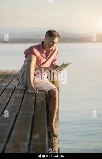 Mature man using digital tablet on pier of lake, Bavaria, Germany - Stock Image