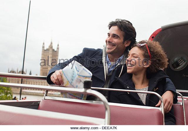 Couple riding double decker bus past Parliament Building in London - Stock-Bilder