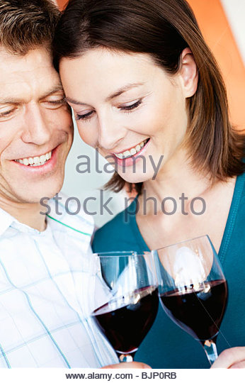 Couple clinking glasses of red wine - Stock Image