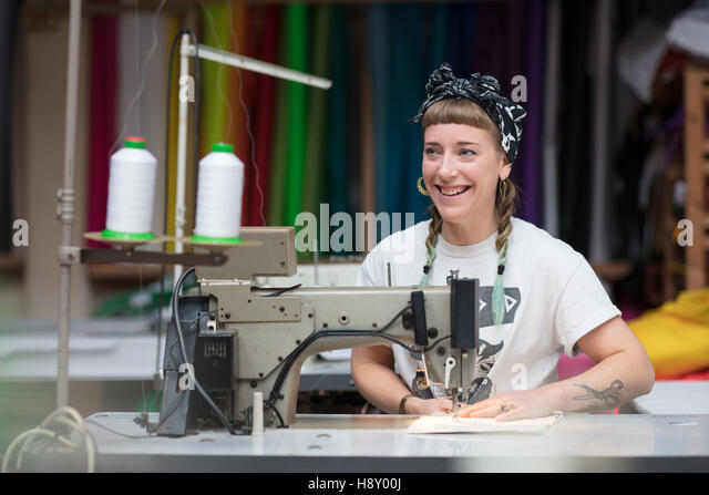 Young tattooed seamstress sewing in a factory environment - Stock Image