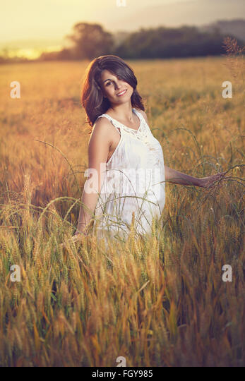 Beautiful woman poses in a field at sunset. Summer season portrait - Stock Image