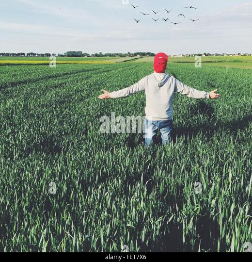Rear View Of Man With Cap Against Sky On Grassy Field - Stock Image