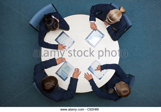 Students in school uniforms using digital tablets at round table - Stock Image