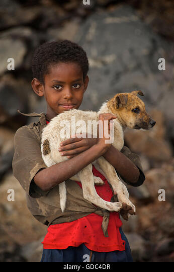 Ethiopian boy holding timid pet dog. The road to Debark, Ethiopia. - Stock Image