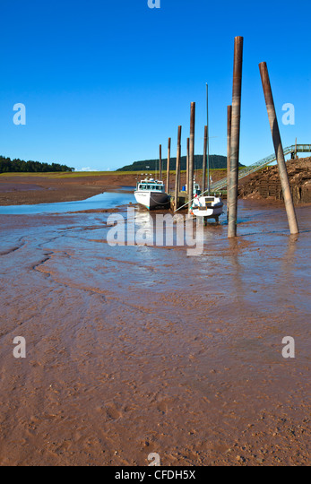 Fishing boats tied up at wharf at low tide, Five Islands, Nova Scotia, Canada - Stock Image