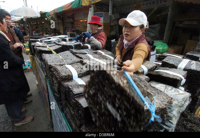 (dpa) - A vendor reaches for a package of dried seaweed at the fish market in Busan, South Korea, 19 December 2004. - Stock Image
