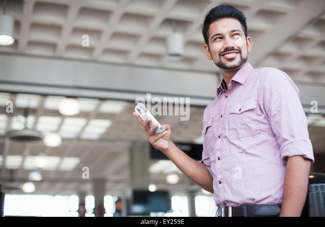 Low angle view of young man using smartphone in train station - Stock Image