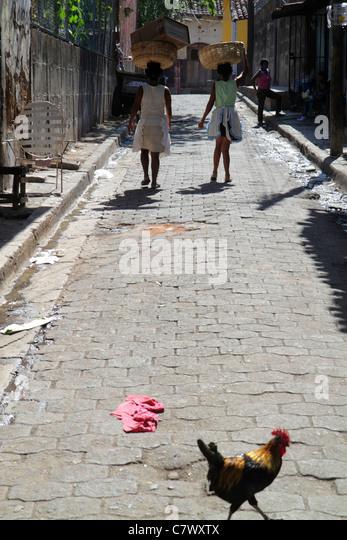 Nicaragua Granada Calle Atravesada shopping market narrow street cobblestone rooster chicken crossing girls walking - Stock Image