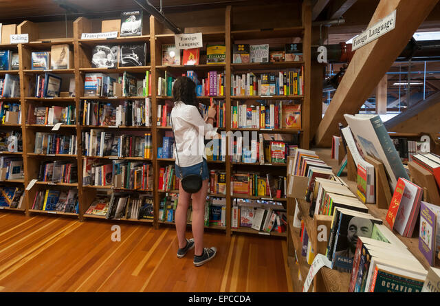 Girl browsing the foreign languages section of the Elliott Bay Book Company in Capitol Hill, Seattle, Washington, - Stock Image