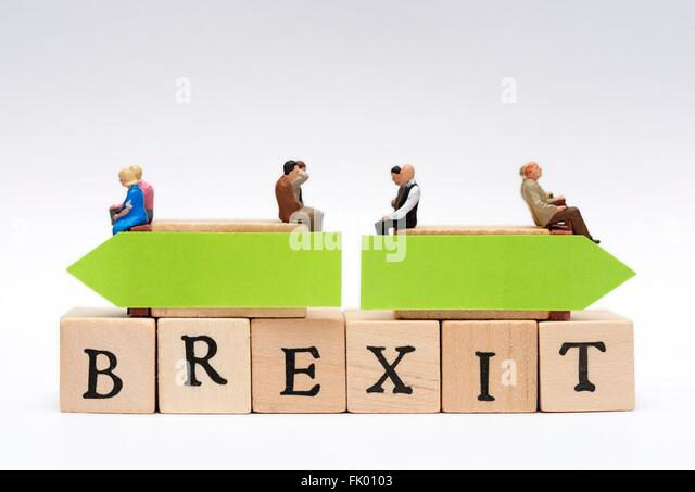 Miniature people sitting on top of the word Brexit with opposing green arrows decision concept - Stock Image