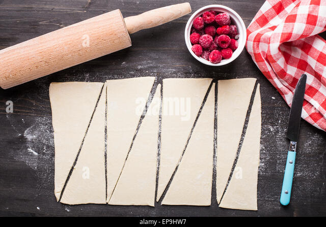 Making homemade croissants stuffed with sweet raspberries - Stock Image