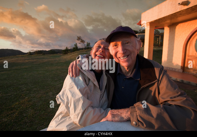 Loving elderly couple smiling at table in mountains - Stock-Bilder
