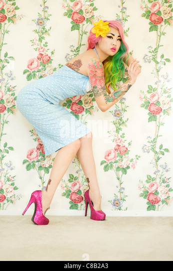 Young woman with high heels posing mysteriously over wallpaper - Stock Image