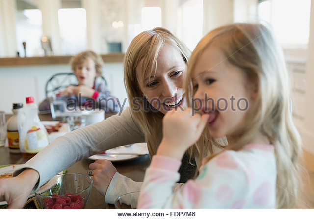 Mother and daughter eating raspberries at breakfast table - Stock Image