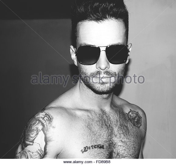 Portrait Of Shirtless Man Wearing Sunglasses At Home - Stock Image
