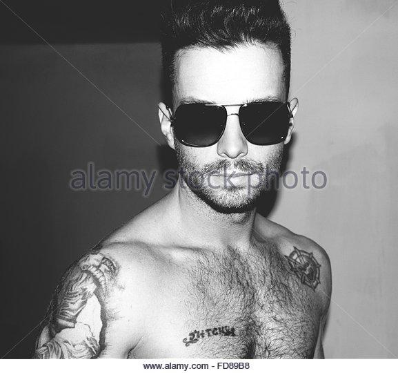 Portrait Of Shirtless Man Wearing Sunglasses At Home - Stock-Bilder