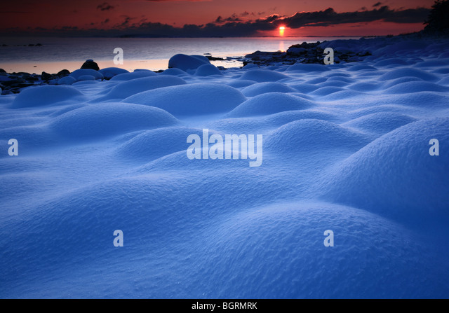 Snow covered rocks and sundown at Larkollen in Rygge kommune, Østfold fylke, Norway. - Stock Image