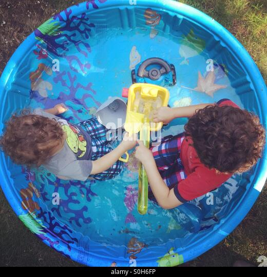 Brothers in the kiddie pool - Stock Image